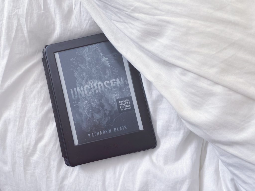 A Kindle lays on a white comforter. The Kindle is showing a digital copy (book cover) of Unchosen by Katharyn Blair.