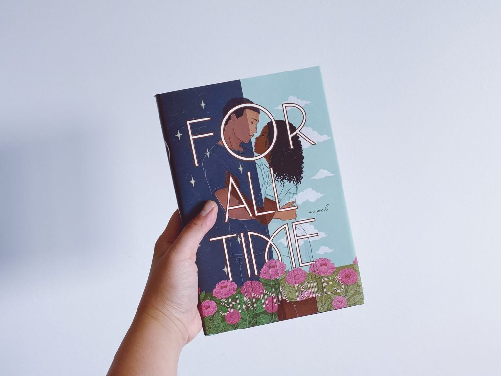 My hand is holding up a hardback copy of For All Time by Shanna Miles against a white background.